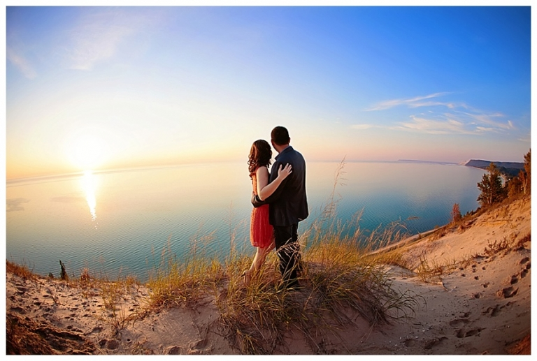 engagement photo in the fall of a couple on the bluffs of sleeping bear dunes at sunset