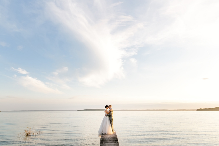 bride and groom on dock at sunset over lake michigan