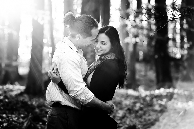 couple in woods for engagement photos with sun shining through