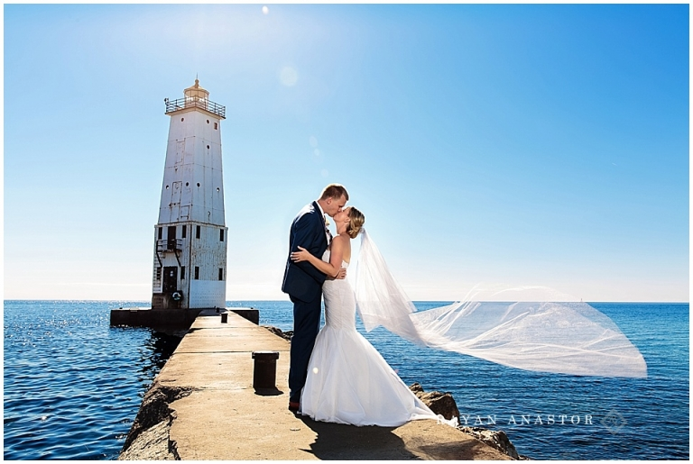 Bride and Groom on pier at Frankfort Lighthouse on lake michigan